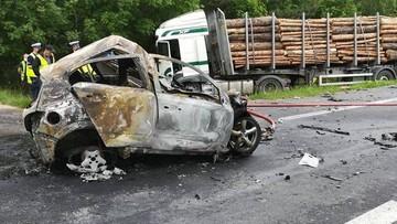 Opel wbił się w tira wyładowanego drewnem i spłonął. Kierowca nie żyje [ZDJĘCIA]