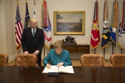 Angela Merkel podpisuje księgę pamiątkową w Białym Domu